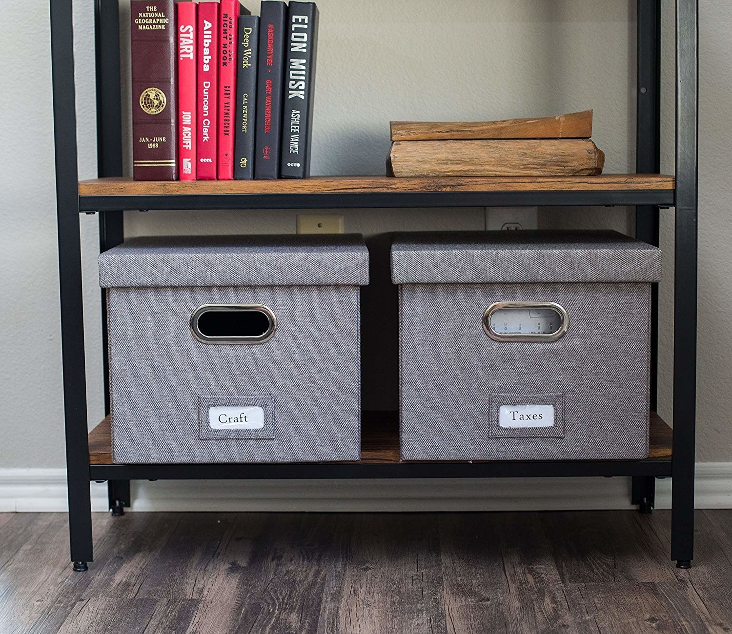 """the two grey fabric-covered boxes on a shelf, one labeled """"craft"""" and the other """"taxes""""; they have chrome-lined handle slots"""