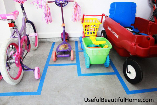 kid's bike, scooter, wagon, pretend shopping cart, and other wheeled toy bin each with a rectangle spot in a blogger's garage
