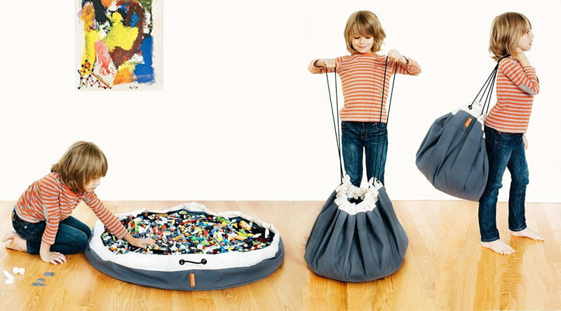 child model playing with circular, open bag full of legos, then pulling the drawstrings, then carrying the bag on their back
