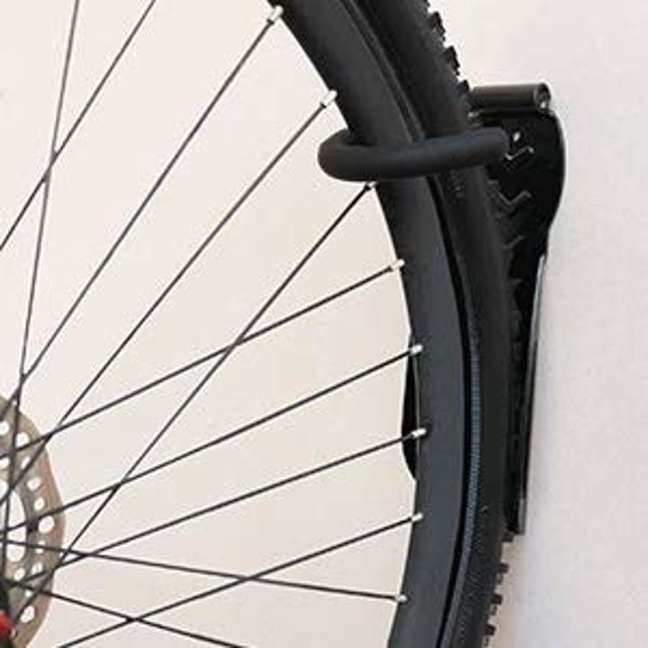 bike wheel supported by hook on wall
