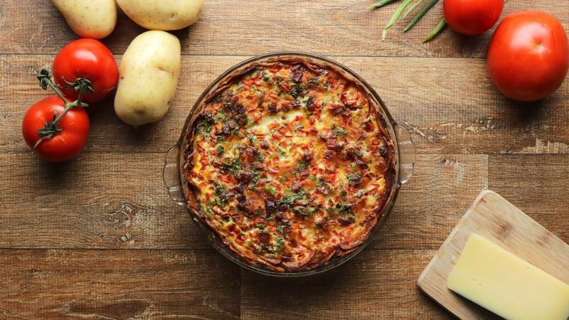 . Pré-aqueça o forno a 180°C (350°F).2. Fatie as batatas em uma mandolina ou com uma faca afiada.3. Em uma tigela média, adicione as batatas cortadas, o queijo parmesão, a pimenta, 1 colher de chá de sal e o azeite. Misture com as mãos para cobrir as batatas.4. Organize as fatias de batata em uma travessa refratária de 22 centímetros, começando no centro e finalizando para fora, sobrepondo ligeiramente as fatias.5. Asse as batatas por cerca de 15 minutos, ou até ficarem macias, mas não douradas.6. Em uma tigela média, misture os ovos, a cebolinha, o leite e a colher de chá de sal restante. Bata até ficar homogêneo.7. Cubra a base de batata com a carne moída, a muçarela, o bacon e o tomate. Despeje uniformemente sobre a mistura de ovos. Se alguma das fatias de batata começar a flutuar, use uma colher para colocá-las de volta no lugar.8. Asse a torta por 30 minutos, ou até que os ovos estejam firmes e as batatas estejam douradas.9. Fatie e sirva.10. Aproveite!