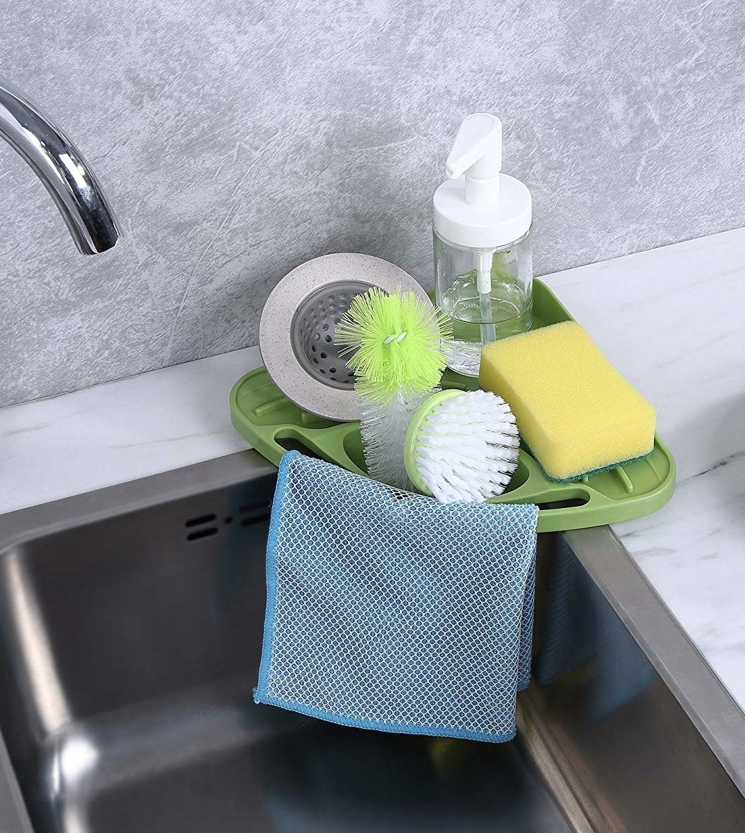 the triangle-shaped green corner tray with drainage area for sponge and soap, over-sink slot for scrub brushes, and small bar to hang dishcloth