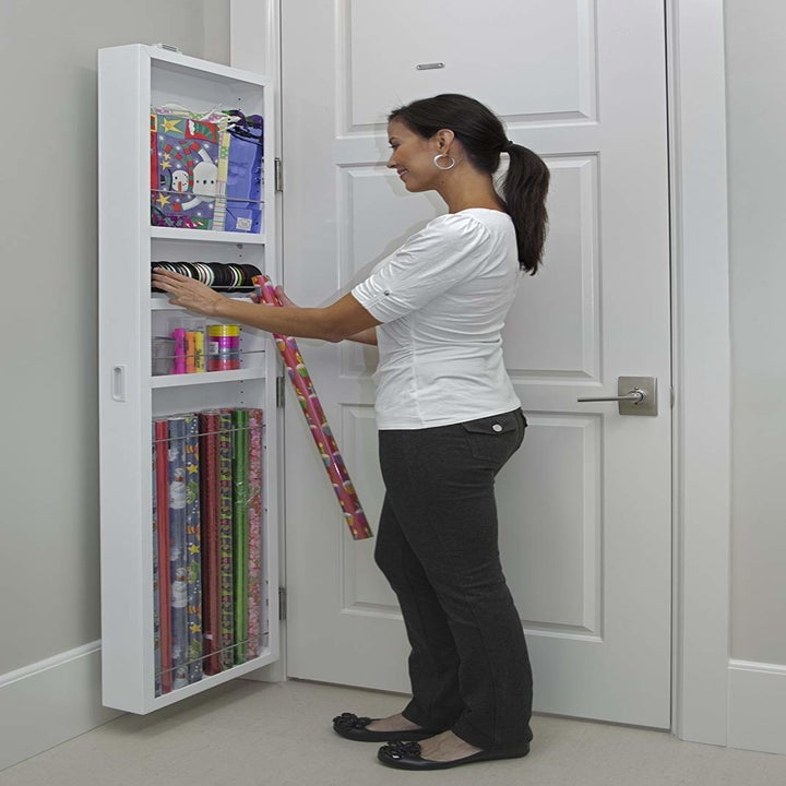 model selecting wrapping paper and ribbon from three-shelf narrow white cabinet