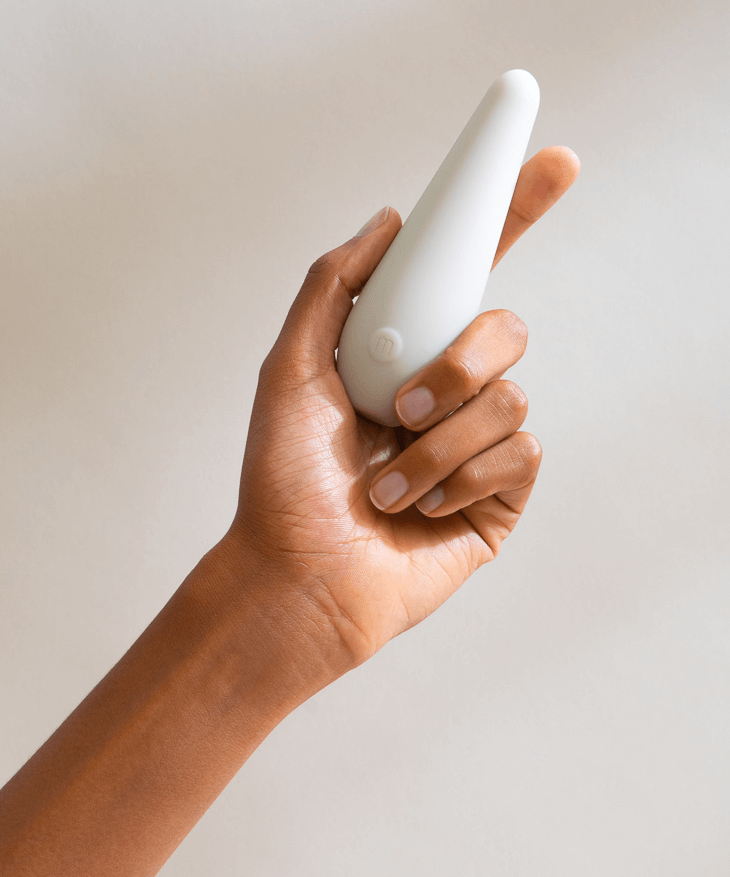 model holding small white oblong vibrator with one button