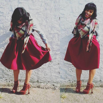 A different reviewer wearing the skirt in red with a scarf and booties