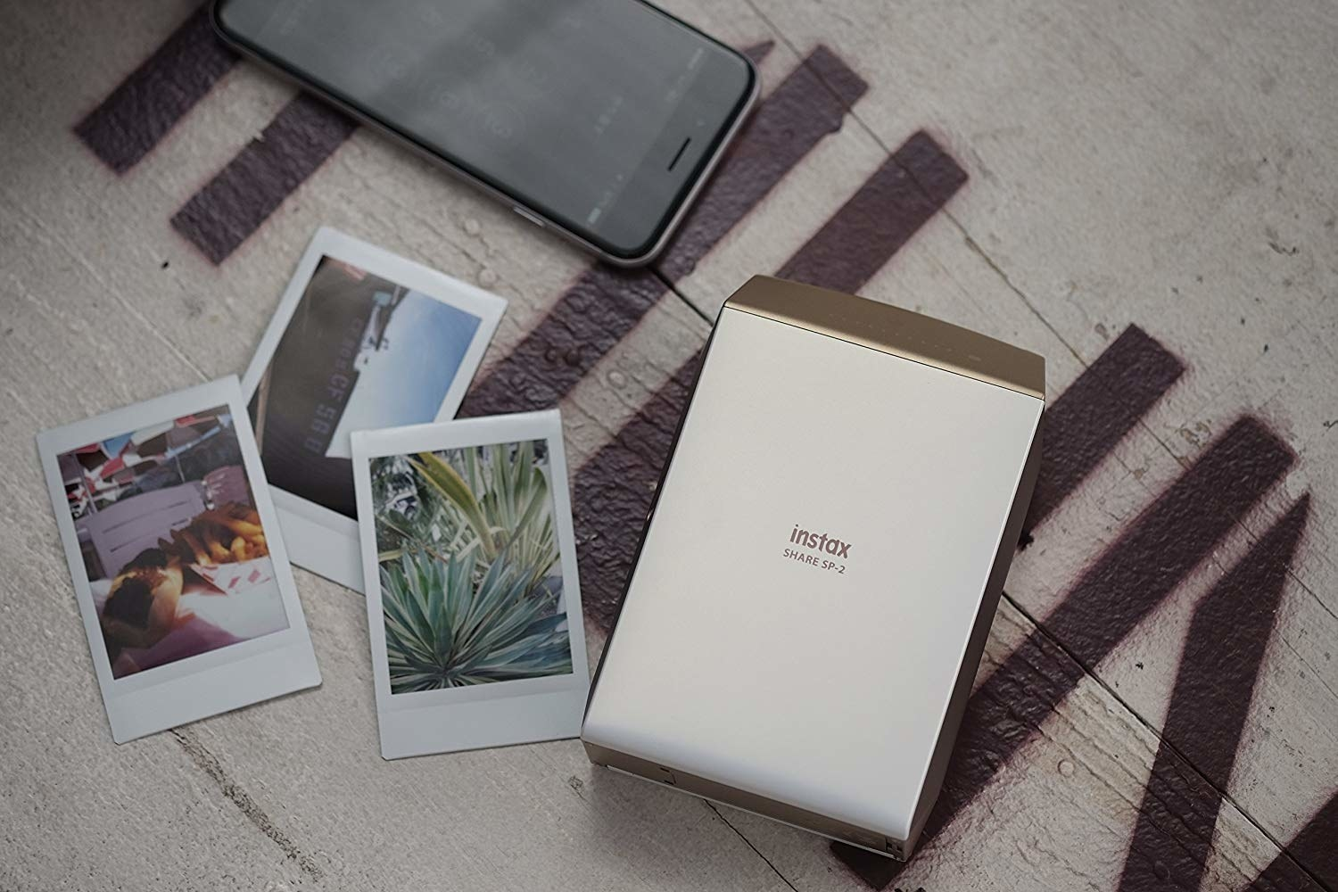 Small printer beside iPhone and photos