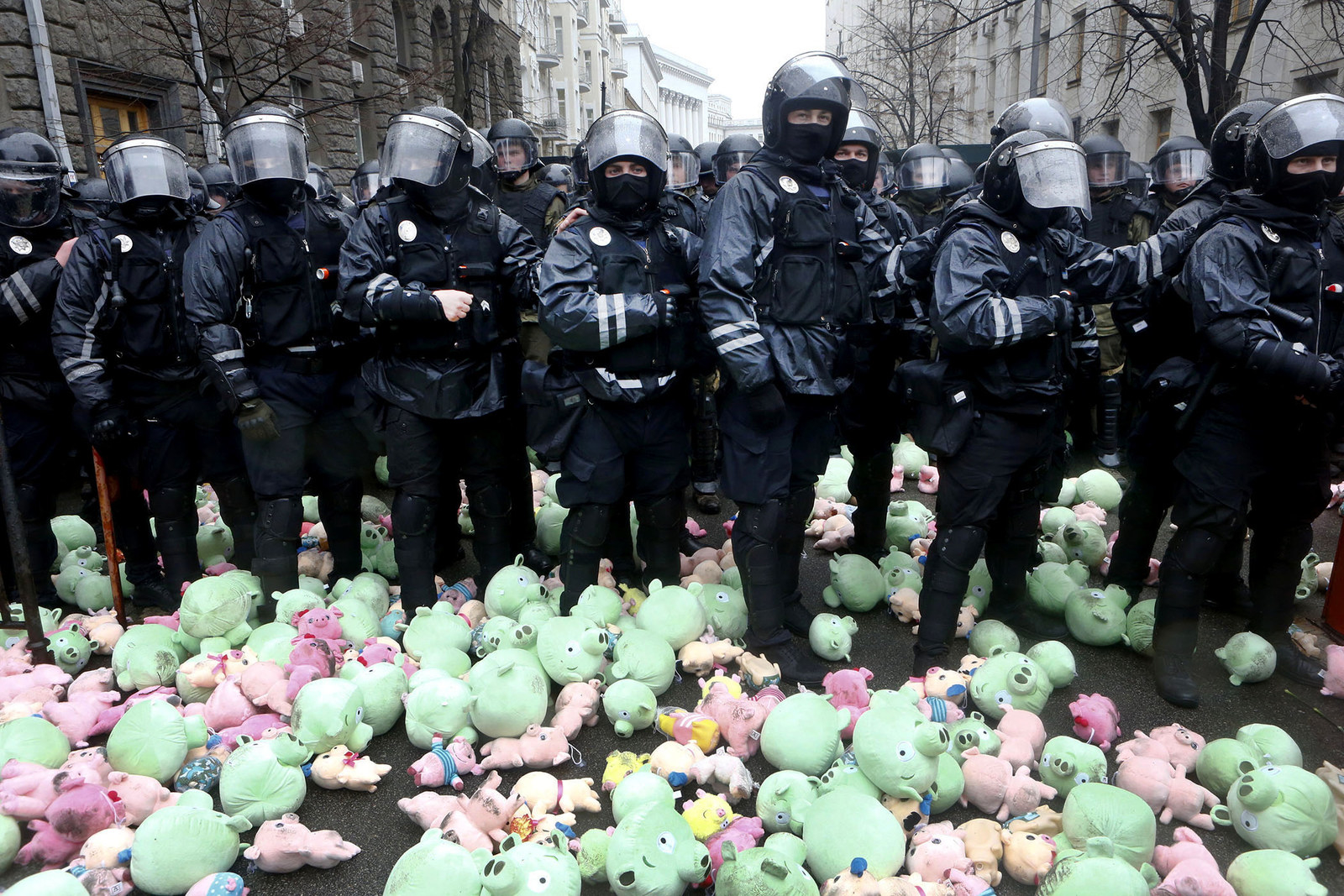 Riot police stand surrounded by toy pigs, thrown by far-right demonstrators during a rally against corruption in front of the Presidential administration's building in Kiev, Ukraine, on March 16.
