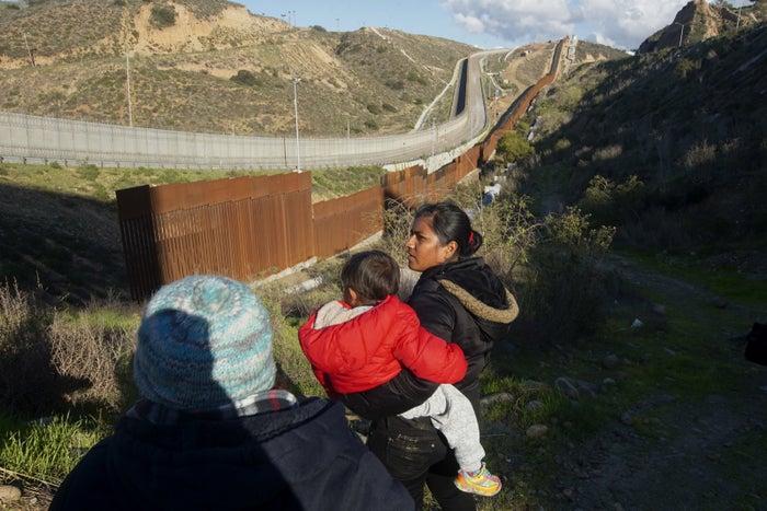 Honduran asylum-seekers walk toward the US–Mexico border fence to cross over.