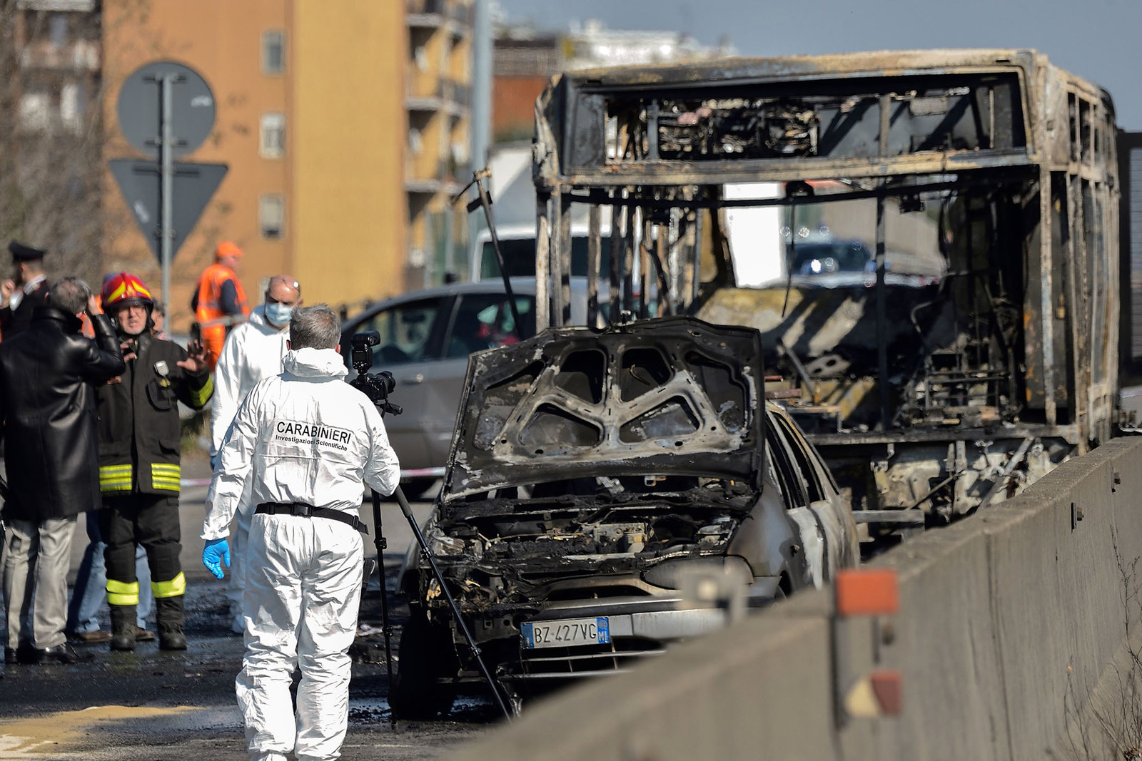 Forensic policemen and firefighters work by the wreckage of a school bus that was transporting some 50 children on March 20, after it was torched by the bus' driver, in San Donato Milanese, Italy. All of the children were rescued from the bus.