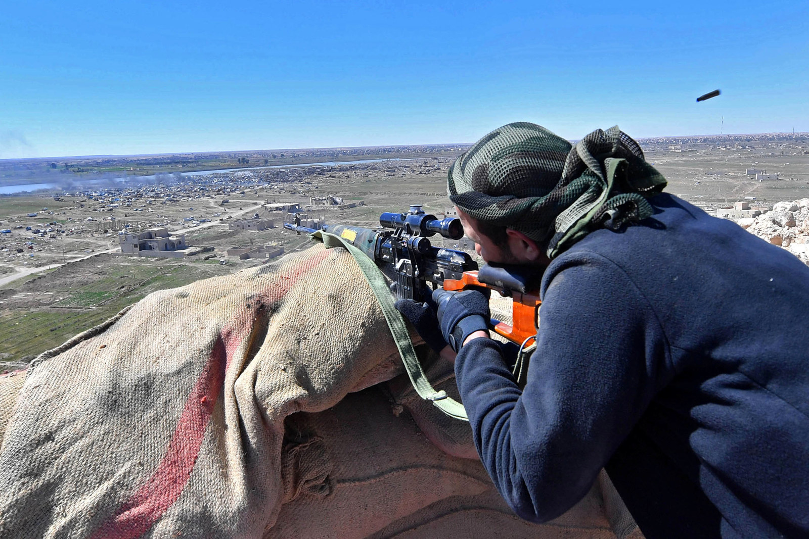 A sniper with the Syrian Democratic Forces opens fire toward Baghouz, Syria, where remaining Islamic State fighters are holding out in their last position on March 18.