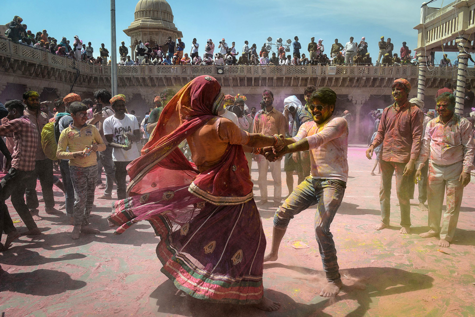 Indian Hindu devotees covered in colored powder dance as they celebrate Holi at a temple in Nandgaon, India, on March 16.