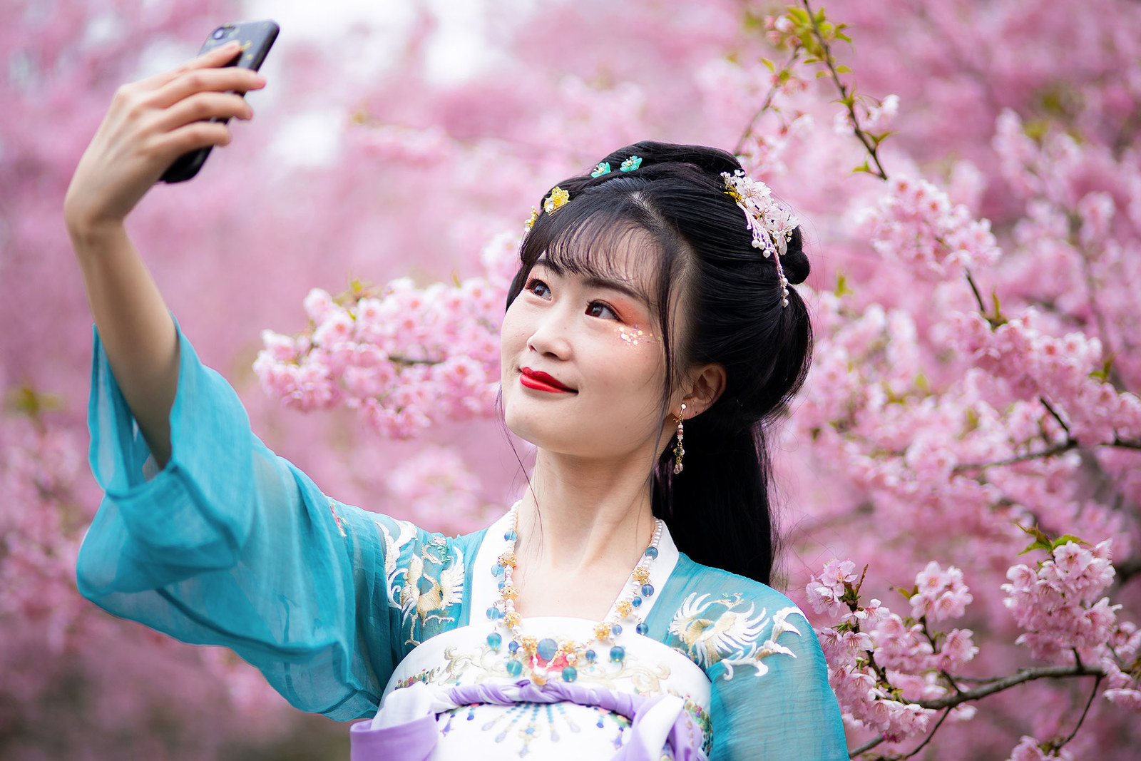 A tourist wearing Hanfu takes a selfie with cherry blossoms at the Nanjing Zhongshan Botanical Garden on March 17, in Nanjing, China.