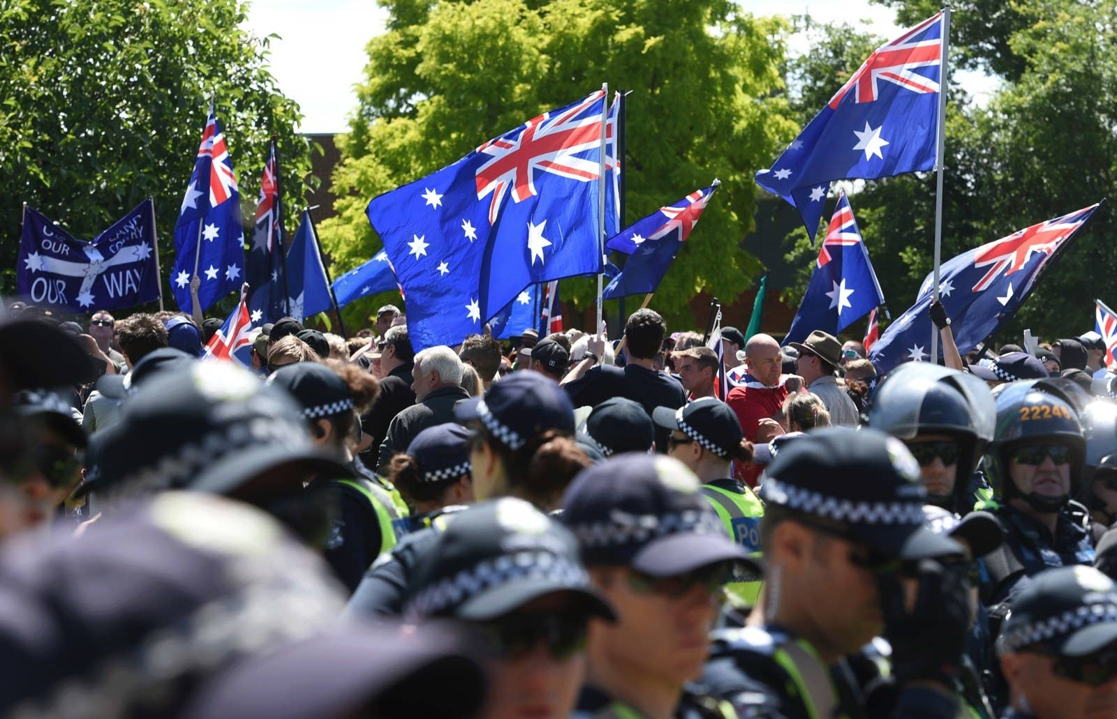 Anti-Islamic Reclaim Australia protesters wave flags and placards as they leave a rally against plans for a mosque being build in Melton, Sunday, Nov. 22, 2015.