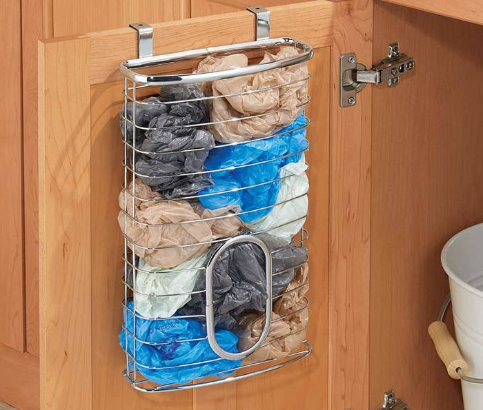 """It can hold up to about 50 bags!Promising review: """"I love this so much! I have been looking for something for all of the grocery bags I keep! We use these for our bathroom trash bags. This little thing is a awesome. And my kids can easily reach inside and get a bag out! Love it!"""" —Lindsey T.Get it from Amazon for $13.99 (available in eight finishes)."""
