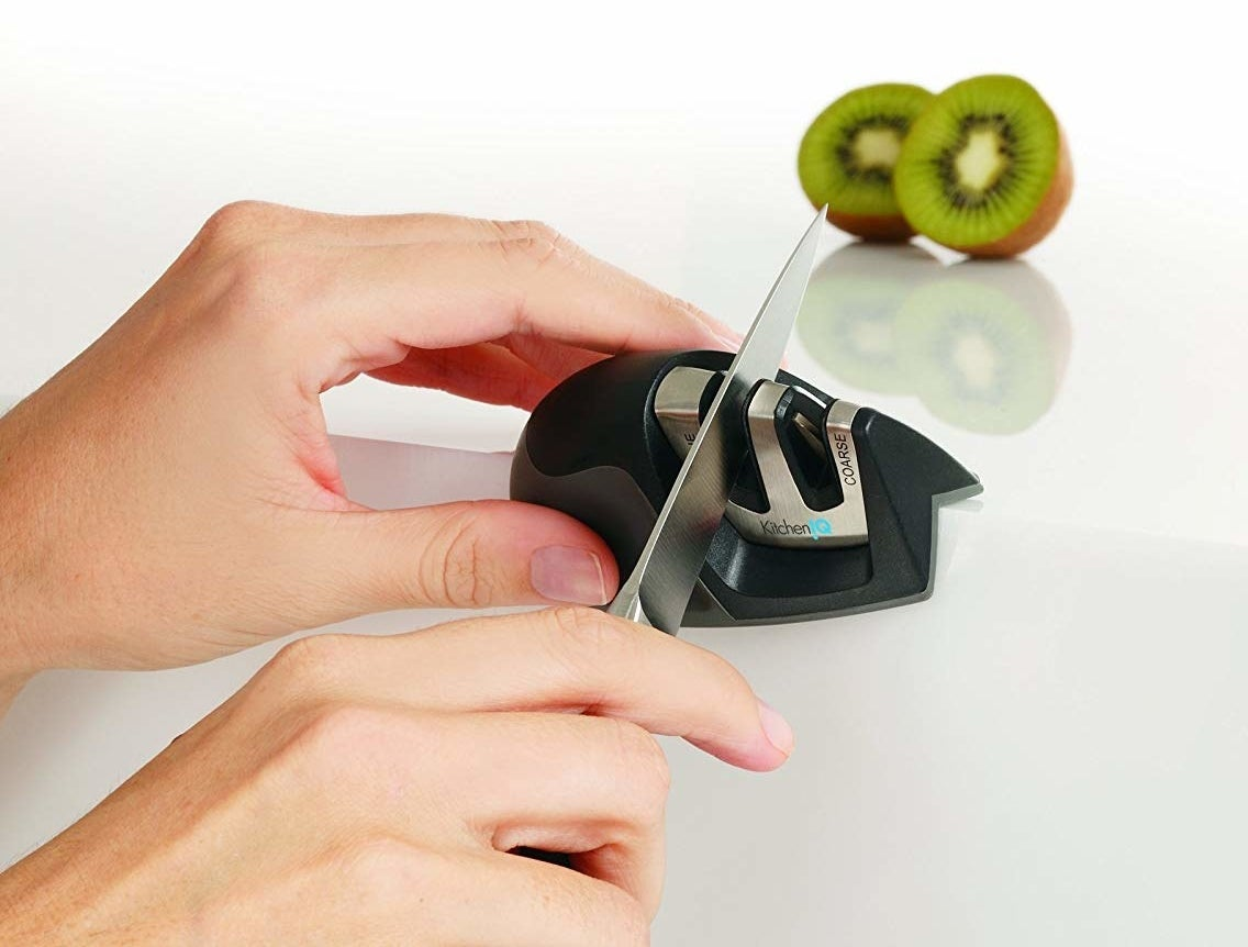 Hands holding the indented sharpener in black on the edge of a counter and sharpening a knife in one of the two slots