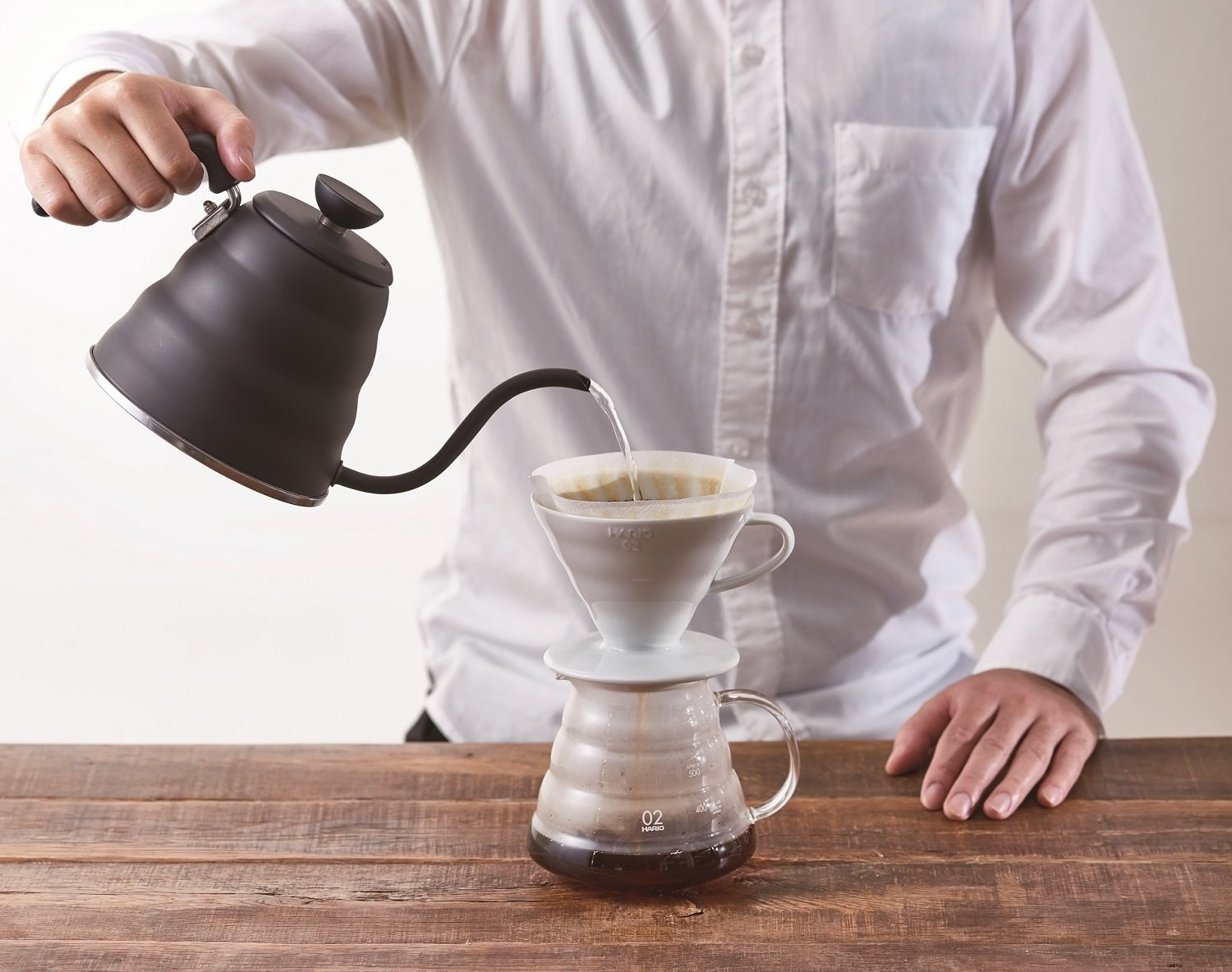Matte black gooseneck kettle being used for pour over