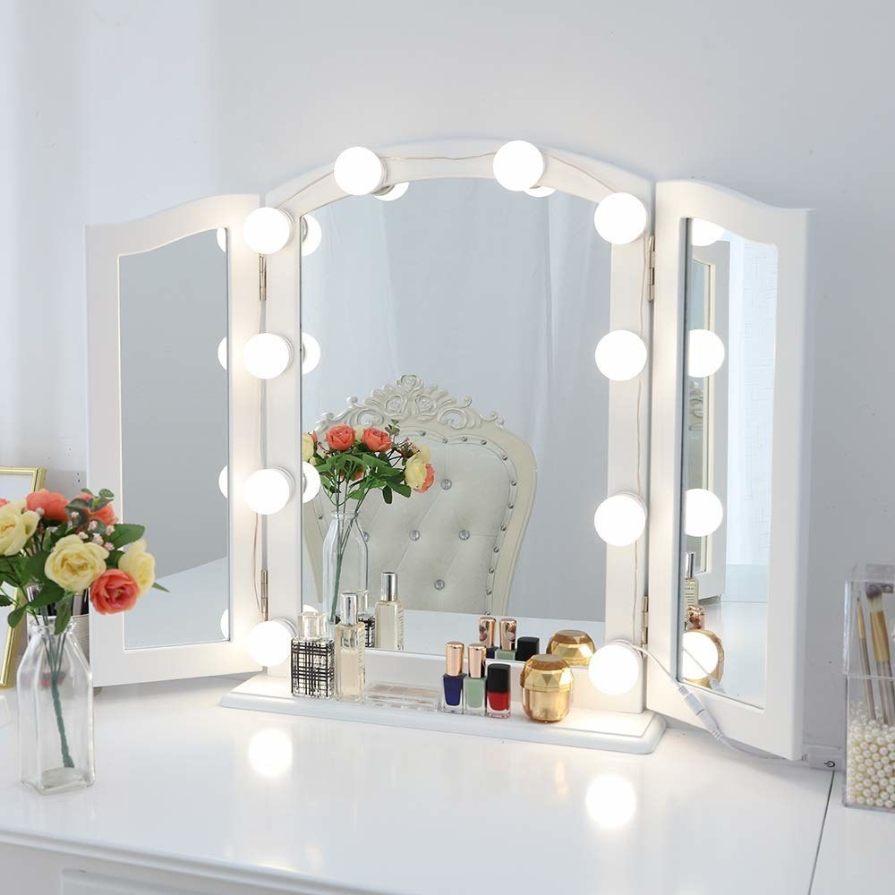 a vanity mirror surrounded by bulb lights