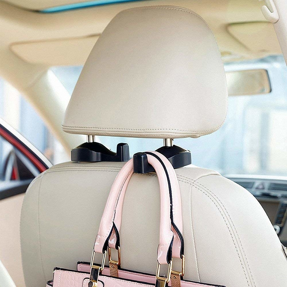 back of a car seat with the hooks attached to the head rest with a bag hanging from it