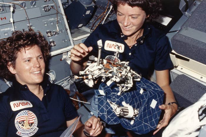 NASA astronauts Kathryn D. Sullivan (left) and Sally Ride in the Space Shuttle Challenger, showing off their design for a sleeping bag complete with restraints for zero-gravity conditions, 1984.