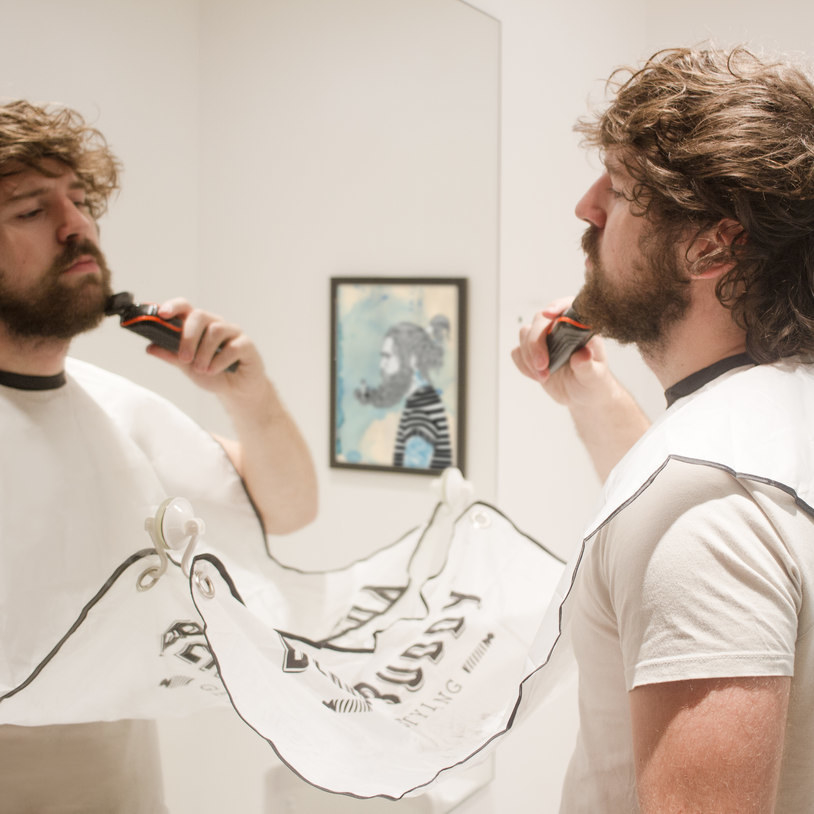 a model wearing a long bib that attaches with a suction cup to the mirror to catch all the beard trimmings as they fall
