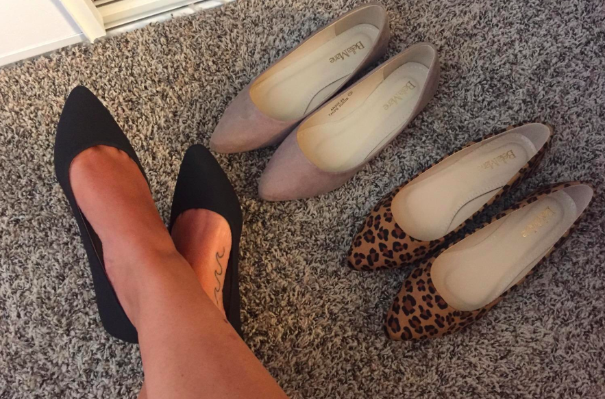 A customer review photo of a person wearing the pointy toe ballet flats in black with two other pairs surrounding her feet.