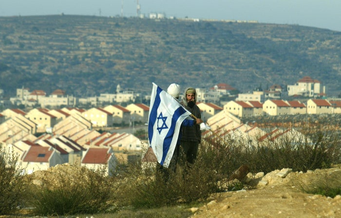 Israeli settlers stand overlooking the Ofra settlement, east of the Palestinian town of Ramallah, in 2006.