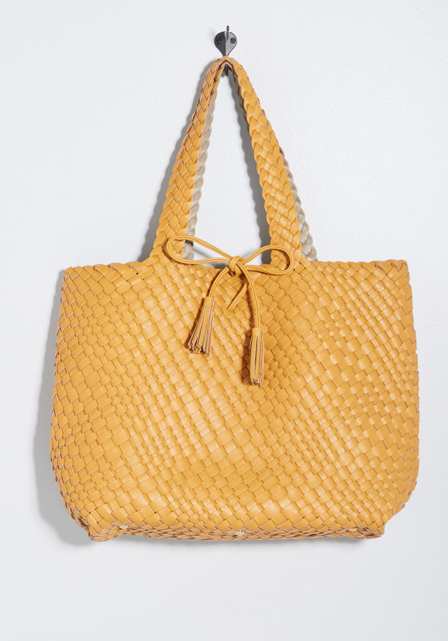 9a3dbc88e A woven tote with a removable pouch sure to make all of your friends want  to braid your accessory collection.