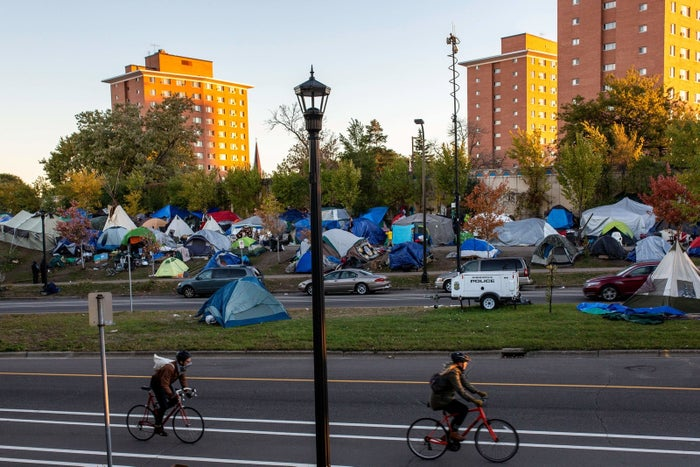 Cyclists pass a tent city near a housing project in Minneapolis.