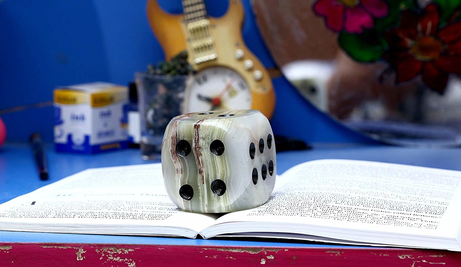 The dice shaped paperweight placed on top of an open book