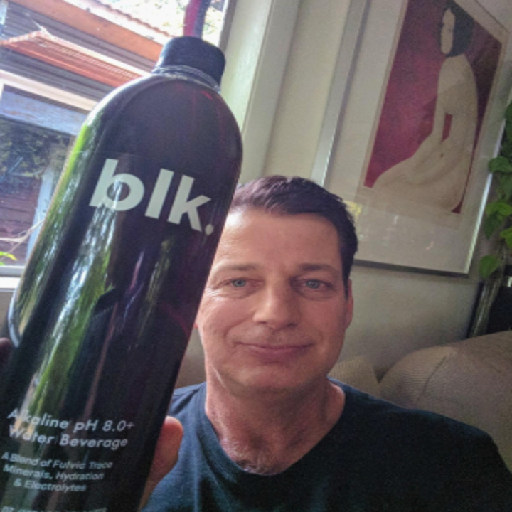 a reviewer holding a black bottle of water