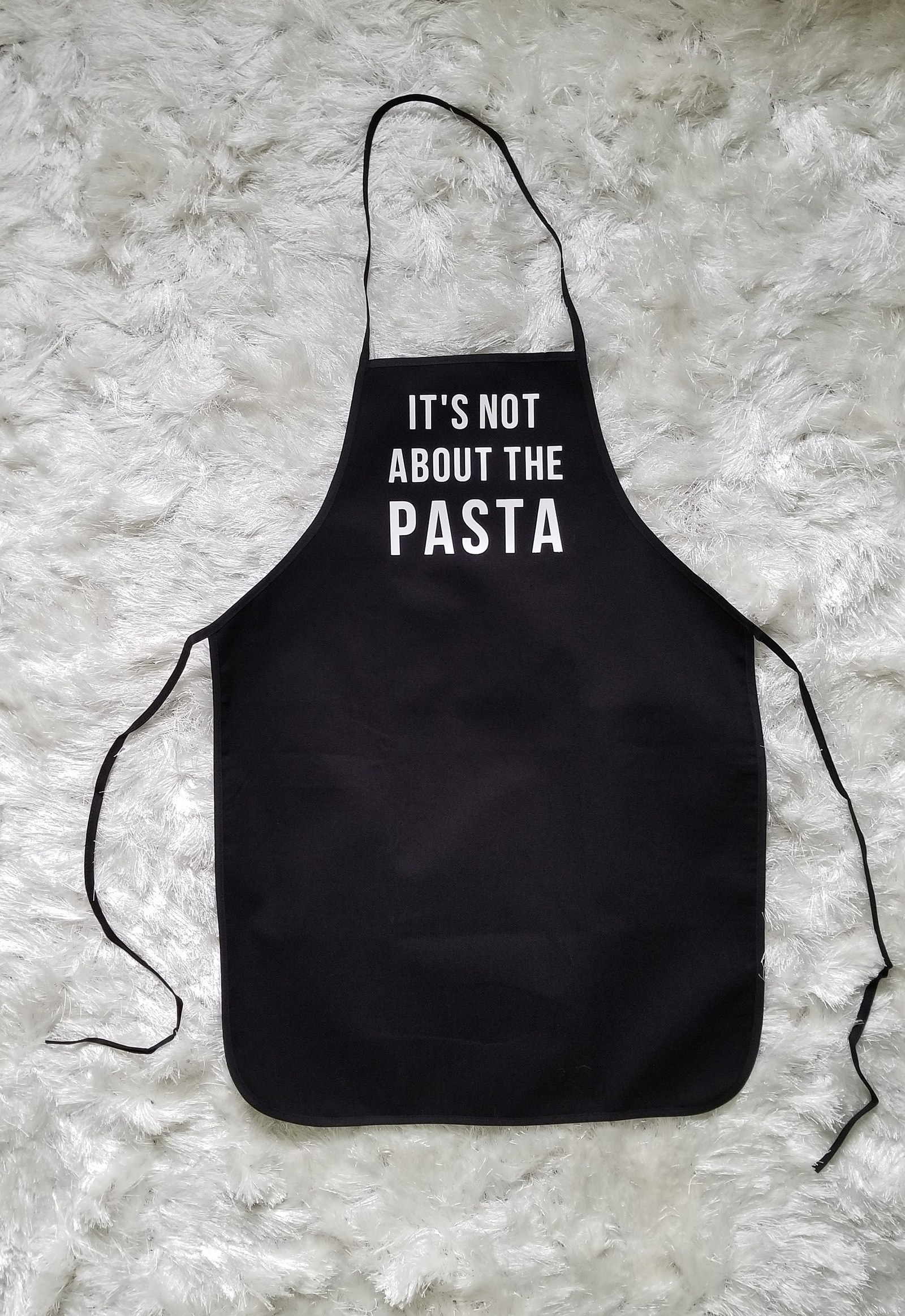 """a black apron that says """"it's not about the pasta"""""""