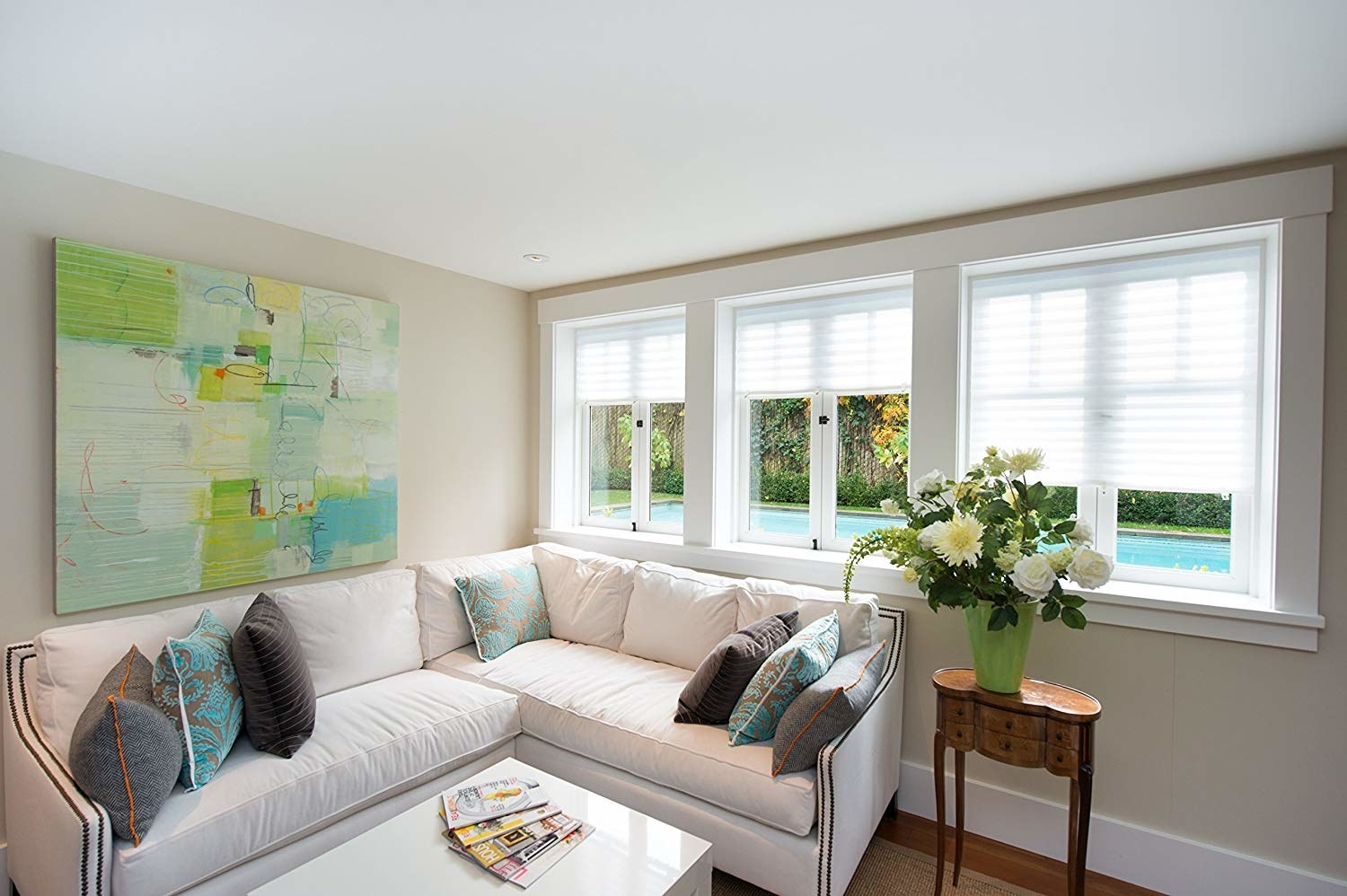 The pleated fabric shades installed on a few windows in a living room.