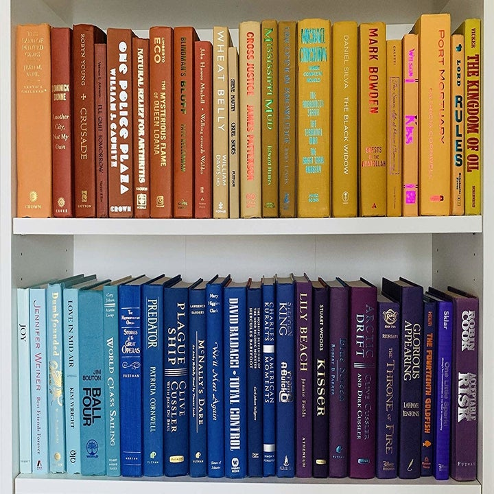 shelf of color-coordinated red, yellow, blue, and purple books