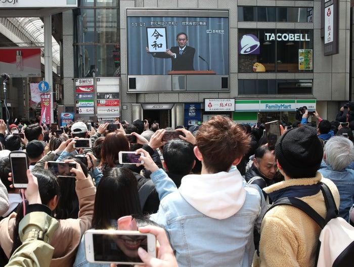 義偉官房長官による新元号発表の様子が映し出された大型ビジョンを見る人たち=1日午前、大阪市中央区道頓堀