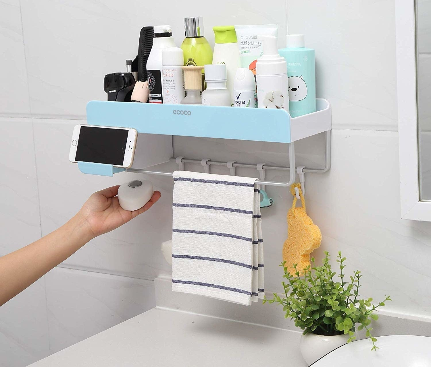 Storage organizer with top bin filled with products, hooks in the back and a tool rod in the front with a place to set a phone on the left side