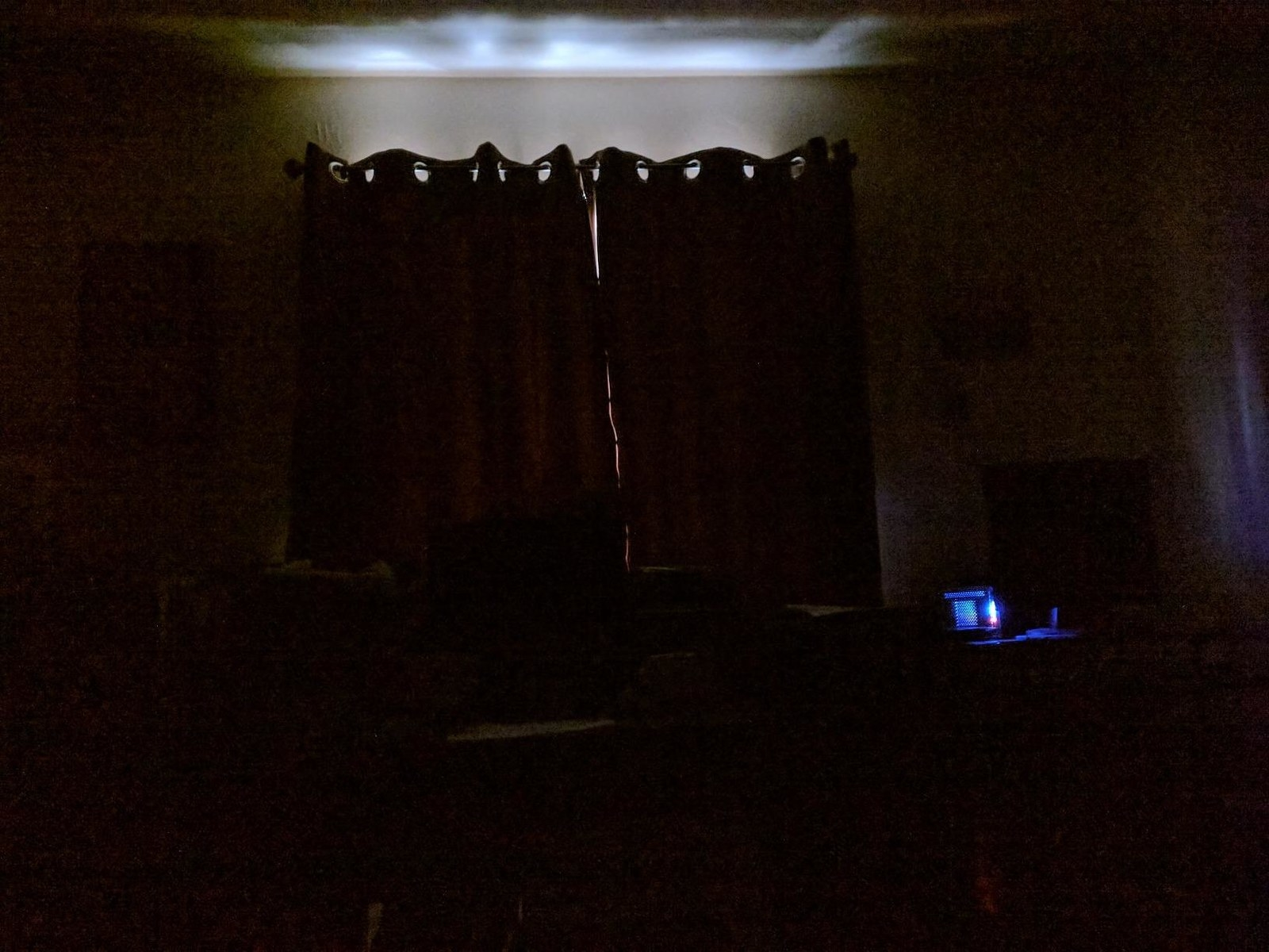 A review image of the curtains blocking out all the daylight, except a teeny strip at the top
