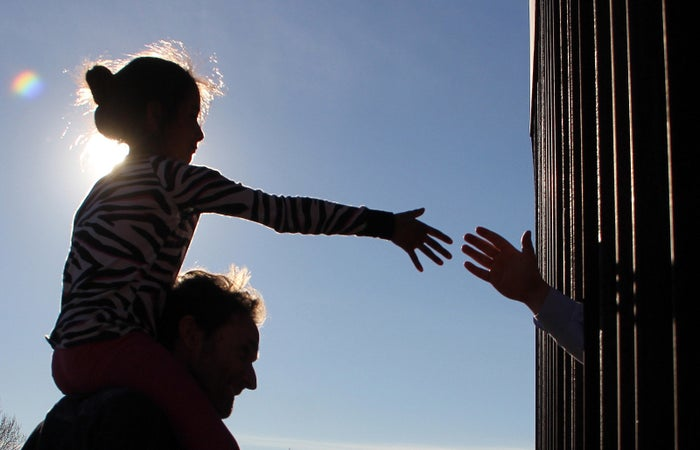 A girl from Mexico touches hands with a person in the US.
