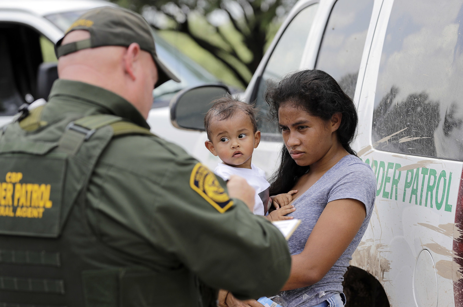 A mother migrating from Honduras holds her 1-year-old child as she surrenders to U.S. Border Patrol agent near McAllen, Texas.