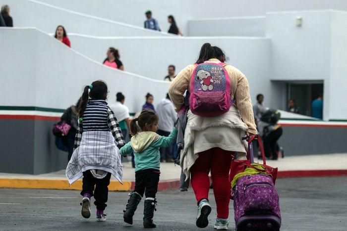 Migrants walk toward the El Chaparral port of entry in Tijuana.