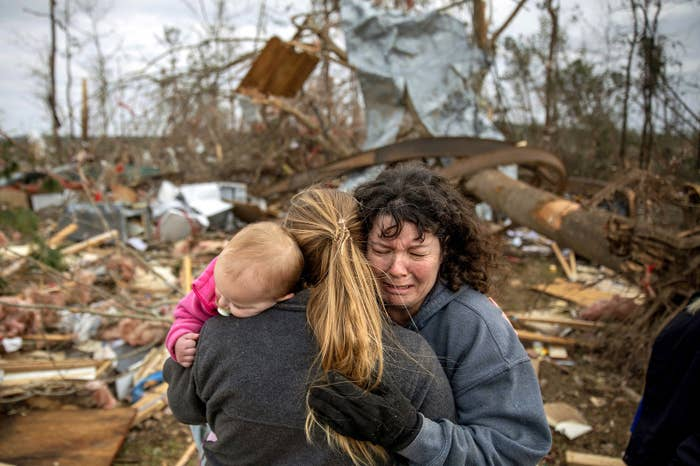 Carol Dean, right, cries while embraced by Megan Anderson and her 18-month-old daughter Madilyn, as Dean sifts through the debris of the home she shared with her husband, David Wayne Dean, who died when a tornado destroyed the house in Beauregard, Alabama, on March 4.