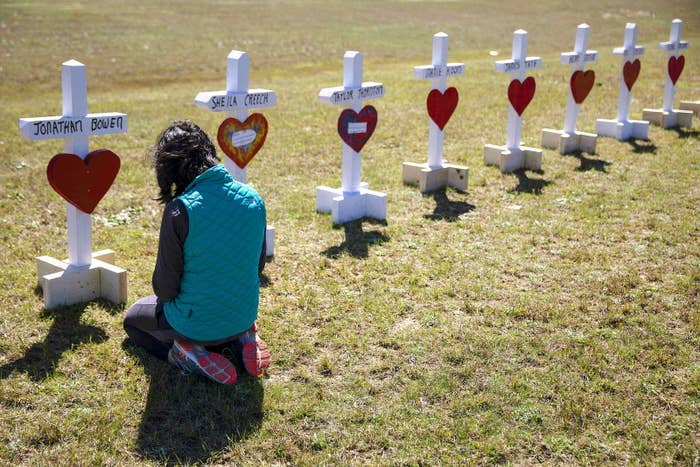 Jessica Taylor prays in front of a cross for Jonathan Bowen, 9, at a makeshift memorial for the victims of a tornado in Beauregard, Alabama, on March 6.