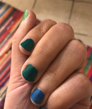 hand with different colored polishes on each nail