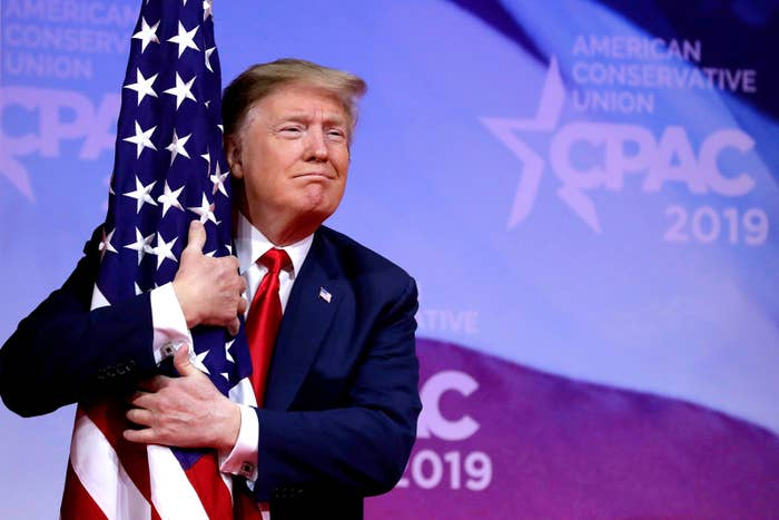 President Donald Trump hugs an American flag at the Conservative Political Action Conference annual meeting at National Harbor near Washington, DC, on March 2.