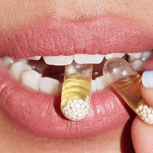 model with pills with tiny white pellets in it