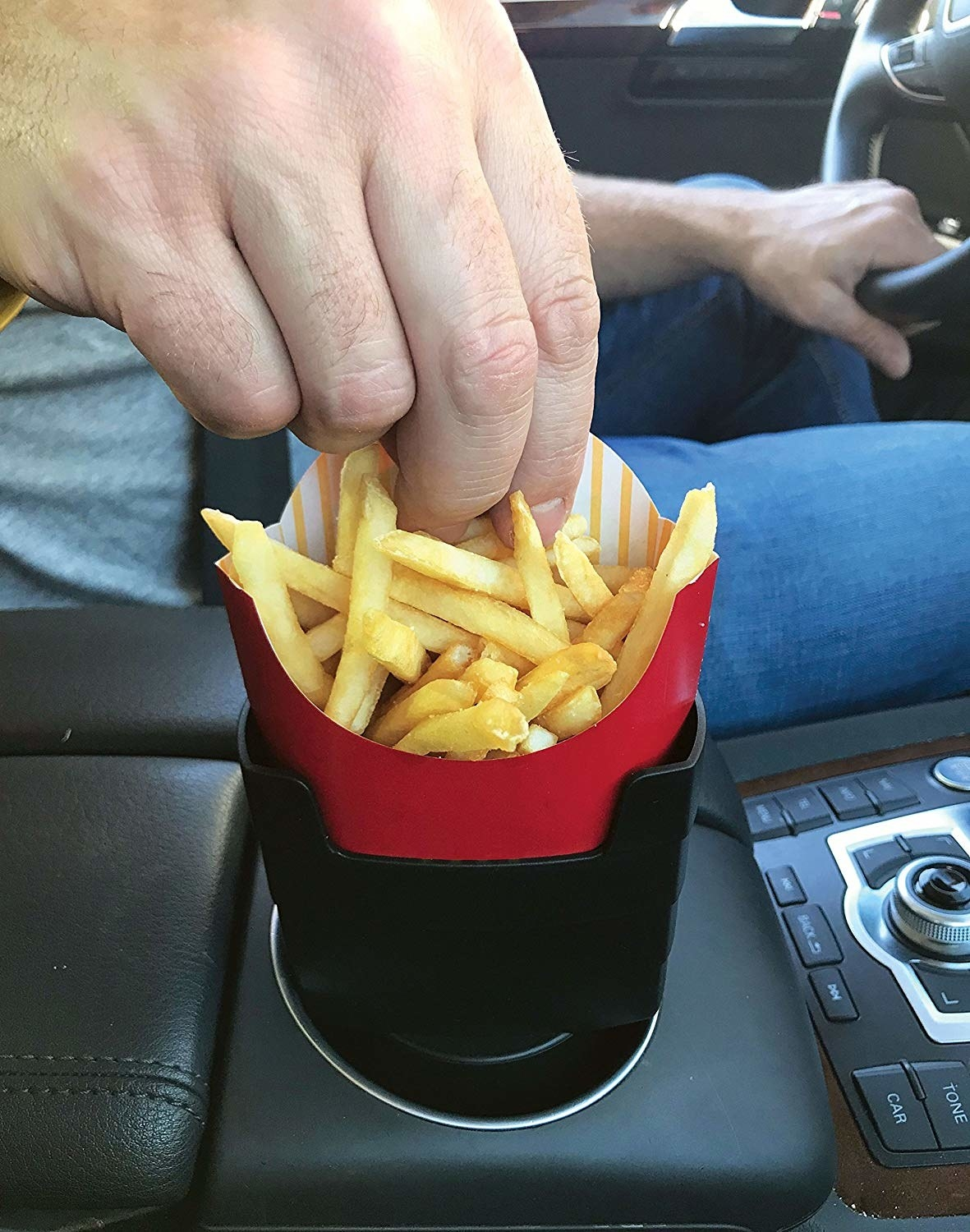 The French fry holder placed in the cupholder of a car.