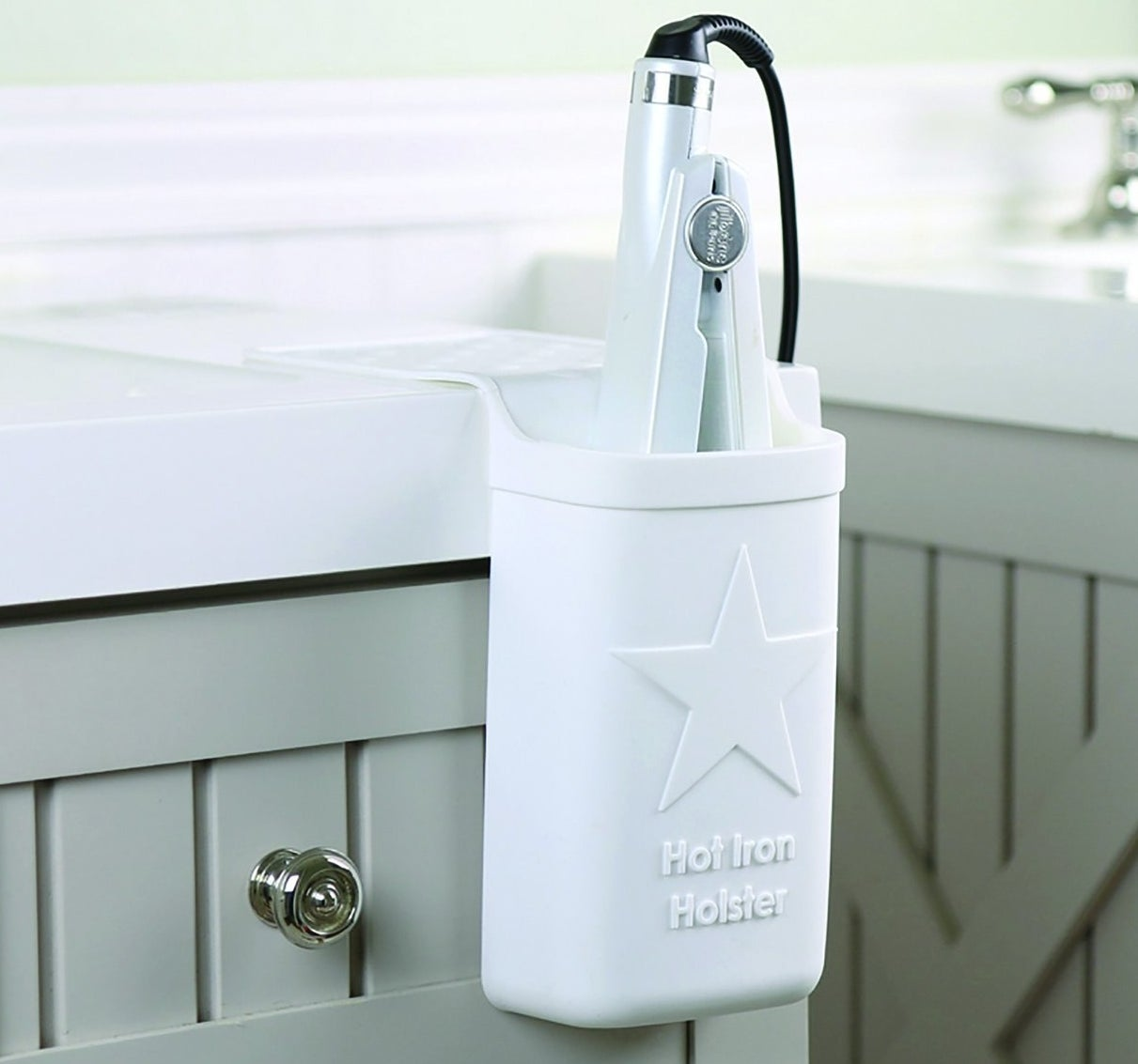 The silicone holster on a bathroom counter with a flat iron placed inside.