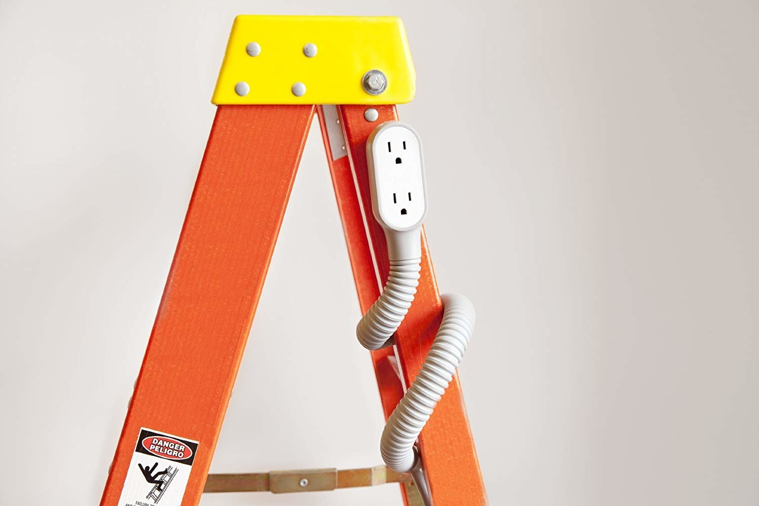 The flexible extension cord wrapped around a ladder.