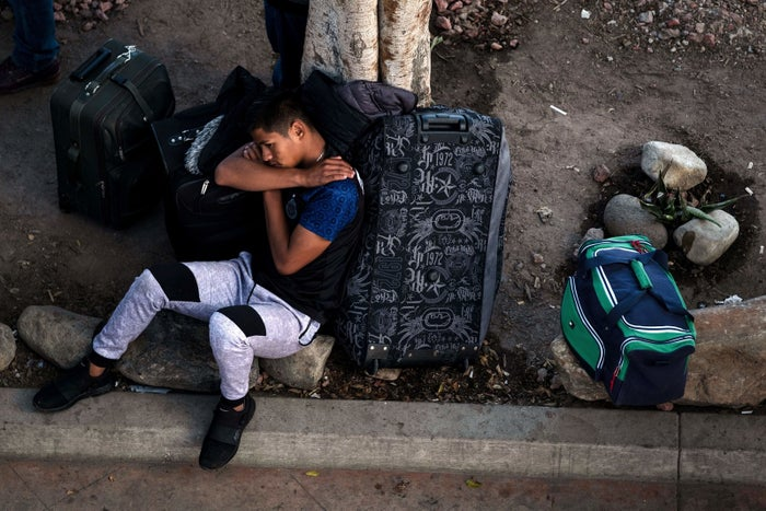 An asylum-seeker rests while he waits in Tijuana for his turn to present himself to US border authorities to request asylum.