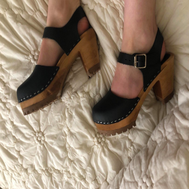 A different reviewer wearing the clogs in black, showing off the stapled-style leather top, wooden heel, and buckle straps at the ankle
