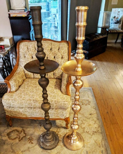 Two candle sticks side by side; one having been treated with the product and looking brand new and the other still rusted over